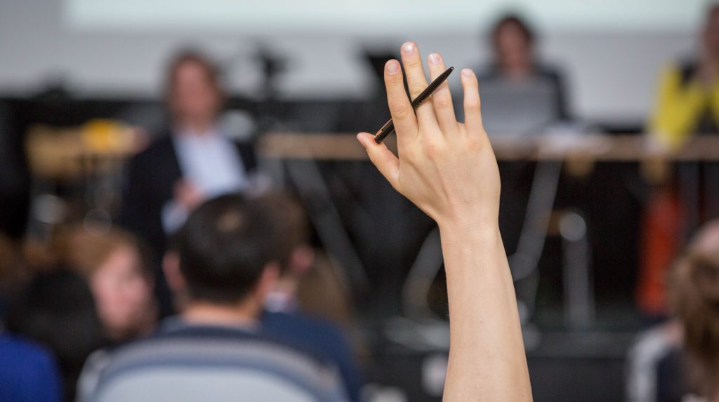 Una mano levantada para hacer una pregunta sobre ASIMUT